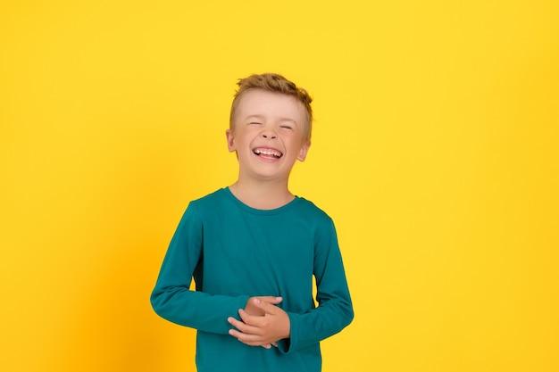 Il bambino ride si tiene le mani sullo stomaco e lo trova divertente