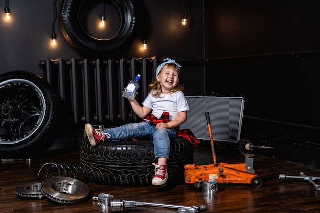 Il bambino ride allegramente in un'officina riparazioni auto tra pneumatici e ruote con una bottiglia di acqua potabile pulita