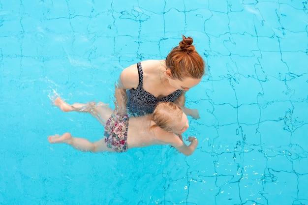 Il bambino impara a nuotare. mamma e figlia stanno nuotando in piscina. vista dall'alto. foto di alta qualità