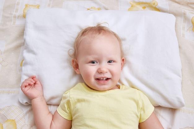 Il bambino si trova sul cuscino e sorride.