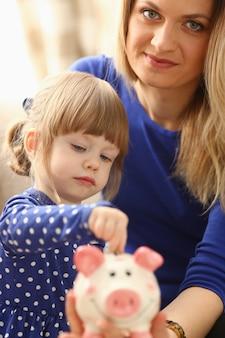 Braccio della bambina del bambino che mette le monete nel porcellino salvadanaio
