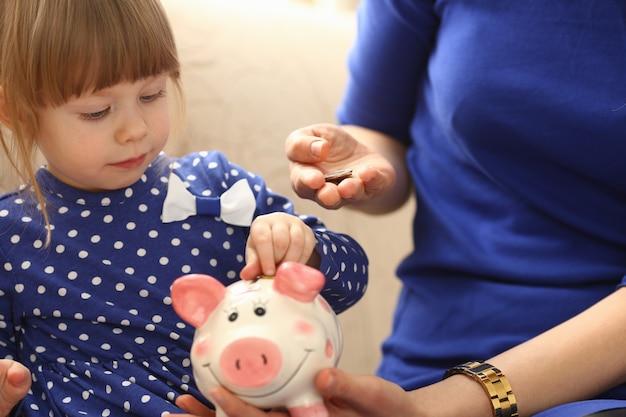 Braccio della bambina del bambino che mette le monete nel salvadanaio