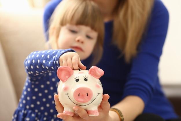 Braccio della bambina del bambino che mette le monete dei soldi del perno nel primo piano di fronte rosa felice della fessura del porcellino