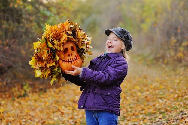 Bambino-una bambina con un berretto e una giacca viola urla fingendo paura e tiene una zucca lanterna di jack con una ghirlanda di foglie sullo sfondo della foresta autunnale