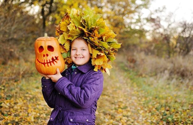 Un bambino, una bambina con un berretto e una giacca viola, sorride e tiene in mano una zucca lanterna jack-o' con una ghirlanda di foglie gialle sullo sfondo di una foresta autunnale. la festa di halloween