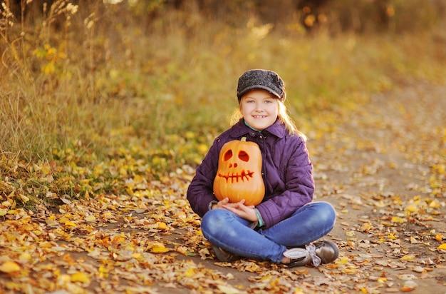 Una bambina, una bambina con un berretto e una giacca viola, sorride e tiene tra le mani la lanterna di zucca di jack sullo sfondo di una foresta autunnale. la festa di halloween