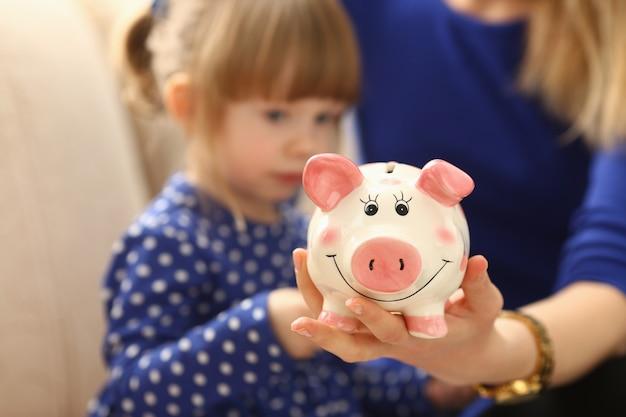 Braccio della piccola donna del bambino che mette le monete nel porcellino salvadanaio