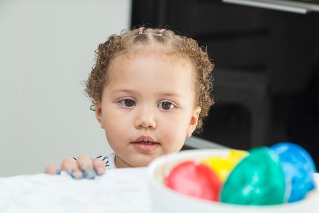 Bambino che esamina ciotola con parecchie uova di pasqua dipinte.