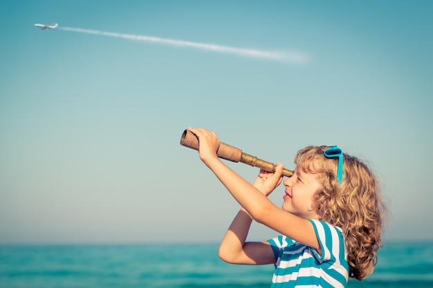Bambino che guarda attraverso il cannocchiale contro il mare e il cielo con un aereo sullo sfondo