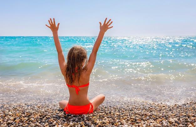Il bambino guarda il mare blu. vista posteriore di una ragazza seduta all'orizzonte del cielo con le mani in alto. spazio per il testo