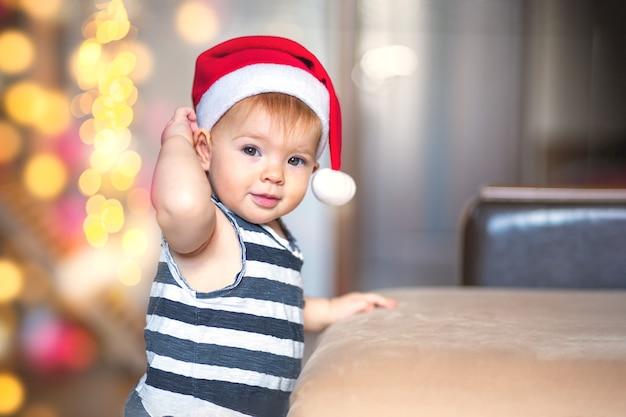 Il bambino guarda la telecamera e corregge il disegno di babbo natale in attesa del miracolo.