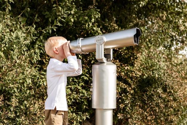Il bambino guarda in un grande telescopio osservazione della natura attraverso un telescopio