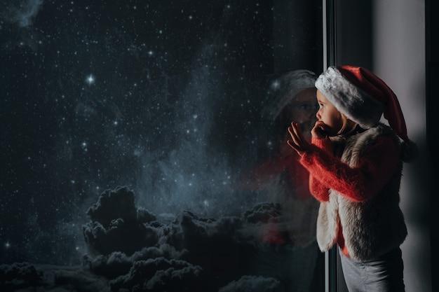 Il bambino guarda fuori dalla finestra il natale di gesù cristo.