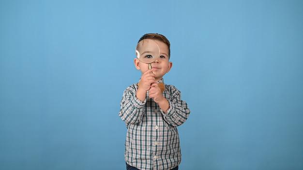 Il bambino guarda attraverso una lente d'ingrandimento. foto di alta qualità
