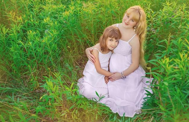 Bambino in un campo di lupino con una madre incinta