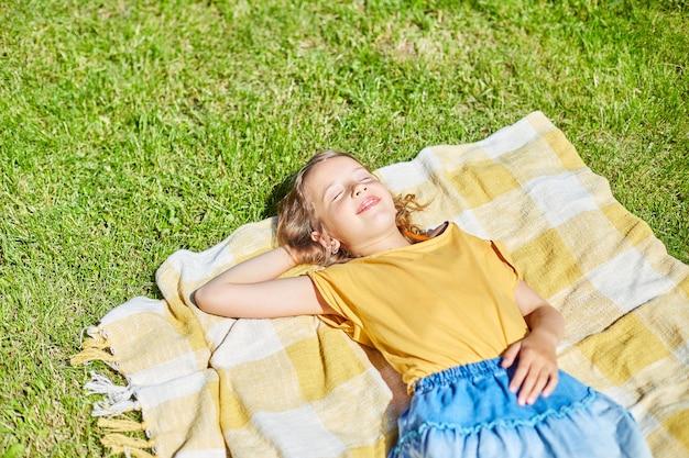 Bambino sdraiato sulla coperta, sull'erba in una giornata di sole, la bambina prende il sole nella casa del cortile