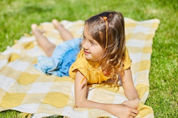 Bambino sdraiato sulla coperta, sull'erba al sole, la bambina prende il sole in cortile