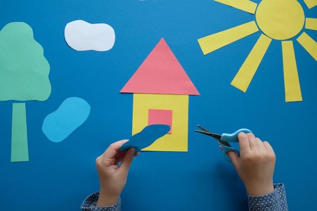 Il bambino fa un'applique con carta colorata