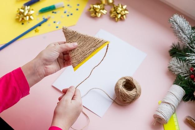 Il bambino fa una cartolina di natale per le vacanze invernali. artigianato fai da te e artigianato per natale fai-da-te