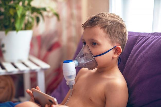 Il bambino produce un nebulizzatore per inalazione a casa. sul viso indossa un nebulizzatore a maschera che inala vapore spruzzato di farmaco nei polmoni del paziente. trattamento della airways con il nebulizzatore ingalatia
