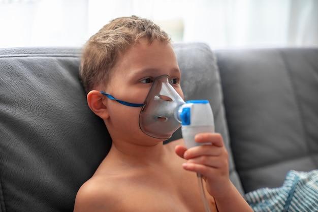 Il bambino produce un nebulizzatore per inalazione a casa. sul viso indossa un nebulizzatore a maschera che inala il vapore spruzzato farmaco nei polmoni del paziente. trattamento della airways con il nebulizzatore ingalatia