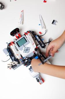 Il bambino fa un robot con pezzi casuali