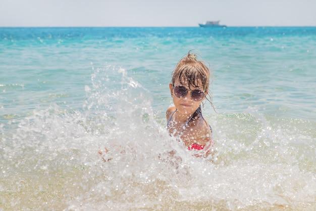 Il bambino fa spray sul mare