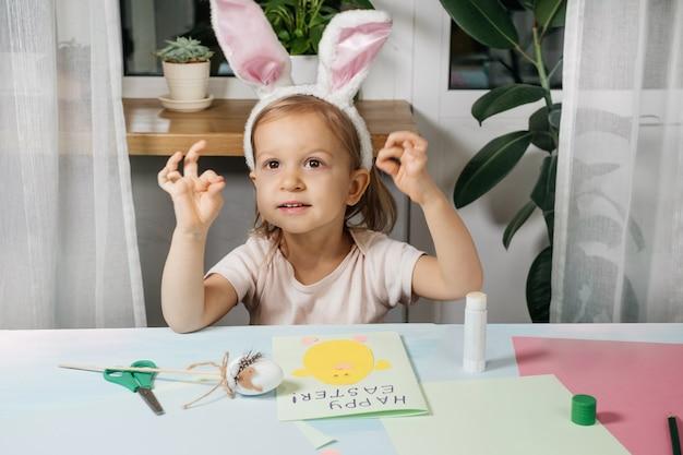 Bambino che fa la carta regalo dell'uovo di pasqua con un coniglietto di carta