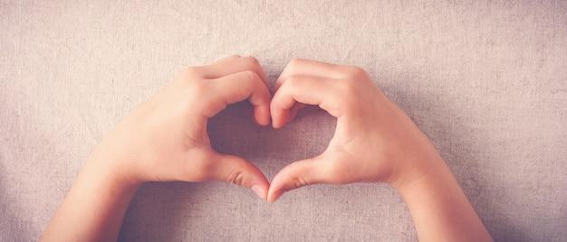 Bambino che fa forma del cuore con le mani