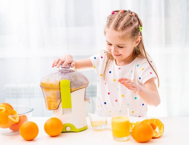 Bambino che produce il succo d'arancia