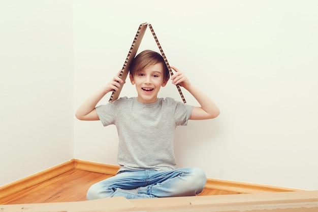 Bambino che fa il simbolo del tetto nella nuova casa. ragazzo carino sogna una nuova casa di famiglia. concetto di adozione.