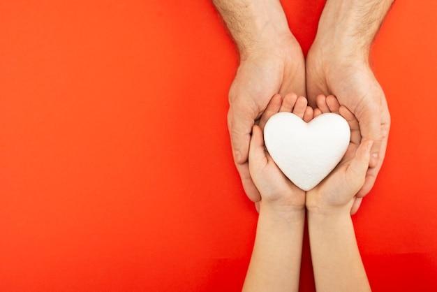 Bambino e uomo che tiene cuore bianco in palme su sfondo rosso, amore e concetto di salute