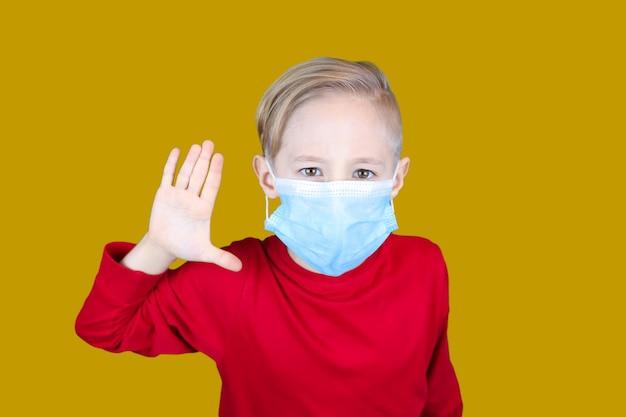 Un bambino in una mascherina medica mostra gesti di arresto su uno sfondo giallo