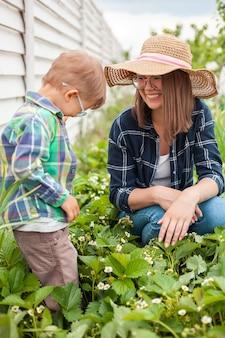 Bambino e madre che fanno giardinaggio nel giardino di piante di fragole nel cortile sul retro