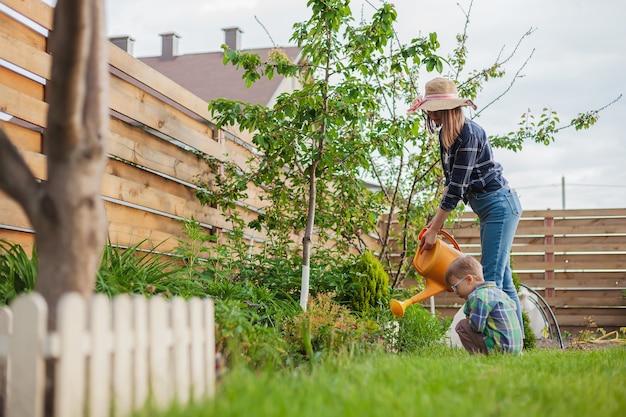 Bambino e madre annaffiatoio innaffiare un giardino nel cortile di casa