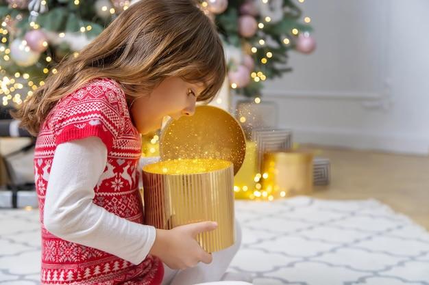 Il bambino apre i regali sotto l'albero di natale. messa a fuoco selettiva. vacanza.