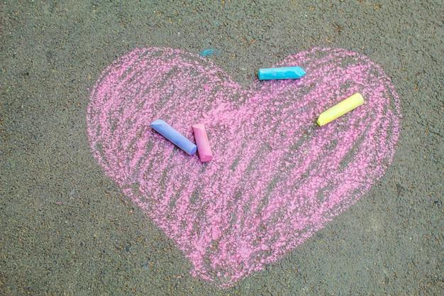 Il bambino ha dipinto un cuore sull'asfalto con il gesso. messa a fuoco selettiva.arte