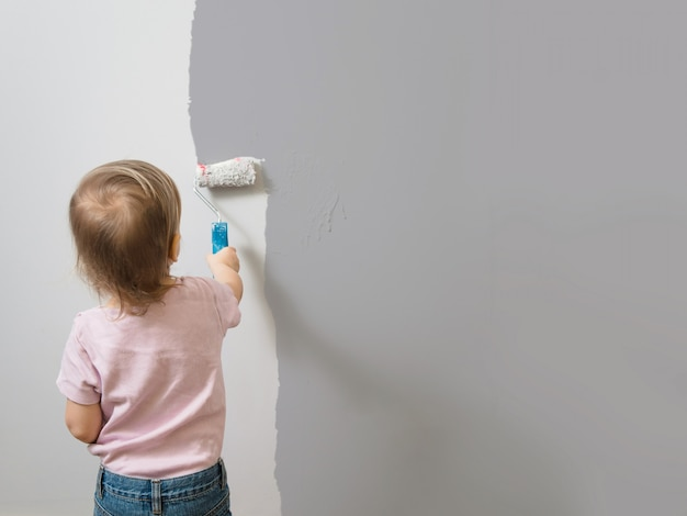 Bambino che dipinge da solo il muro grigio