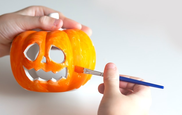 Il bambino dipinge una zucca per halloween su fondo bianco