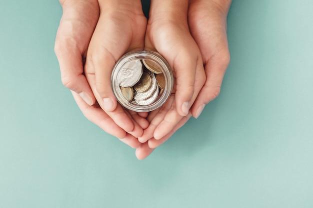 Mani del genitore e del bambino che tengono il barattolo dei soldi, donazione, risparmio, concetto di piano di finanze familiari