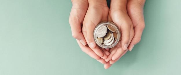 Mani del genitore e del bambino che tengono il barattolo dei soldi, la donazione, il risparmio, il concetto di piano di finanza familiare