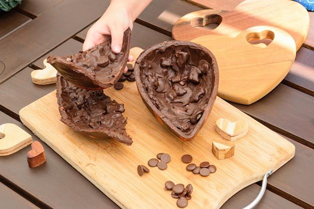 Bambino che prende metà dell'uovo di pasqua di cioccolato fondente con mandorle croccanti. circondato da callette di cioccolato e cuori di legno.