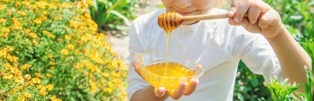 Figlio di un piatto di miele nelle mani. messa a fuoco selettiva.