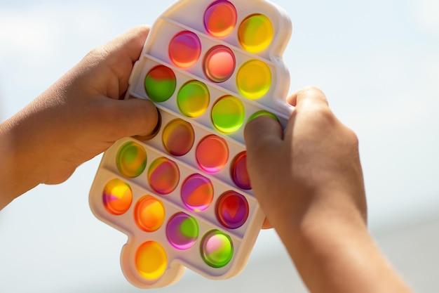 Il bambino gioca con il nuovo giocattolo in silicone che si fa scoppiare sulla spiaggiasemplice fossetta in cornice di plastica