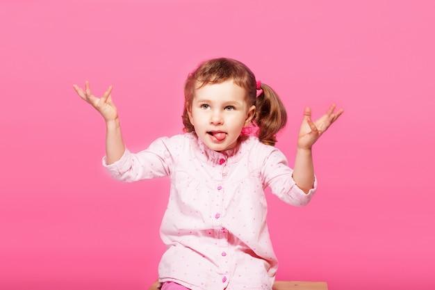 Bambino che gioca la scimmia. piccola neonata che indossa vestiti rosa contro una rosa