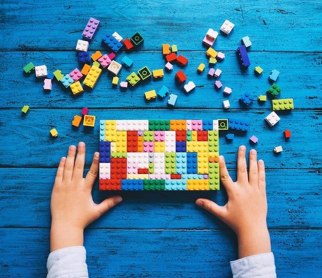 Bambino che gioca e costruisce con mattoncini giocattolo colorati o blocchi di plastica sul tavolo