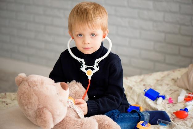 Bambino che gioca al dottore con un giocattolo. pediatra per bambini in età prescolare e all'asilo. concetto di pediatria, assistenza sanitaria e persone