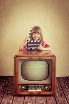 Bambino che gioca in casa. bordo di valvola della holding del bambino divertente. tv retrò. concetto di cinema