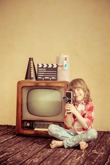 Bambino che gioca in casa. bambino che fa un film con la fotocamera retrò. concetto di cinema