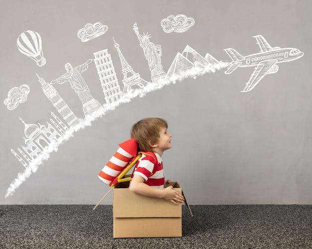 Bambino che gioca in casa. bambino seduto in una scatola di cartone. bambino che sogna di viaggiare. immaginazione dei bambini e concetto di viaggio